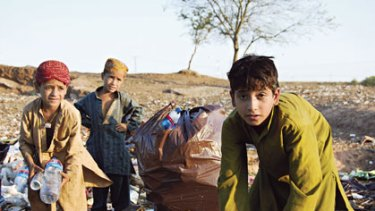 Sifting through the refuse of the rich ... Muhammad Yunis, left, and Habibullah,  right, scavenge for food with another child on a rubbish dump in Islamabad.
