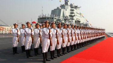 Tension: Sailors on parade in front of China's first aircraft carrier, which was in the confrontation with the USS Cowpen.