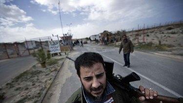 Turmoil ... a rebel fighter in Libya on patrol at an oil refinery in Brega on Thursday.