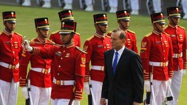 Tony Abbott inspects a ceremonial guard.
