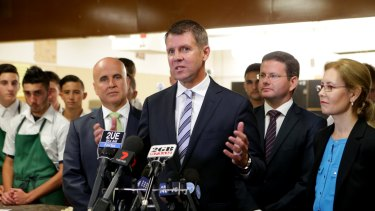 Mike Baird, flanked by ministers Adrian Piccoli and Gabriel Upton, says he expects Tony Abbott to prove wrong those who doubt him because of plummeting approval ratings.