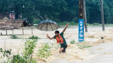 A Nepalese man looses his balance while crossing a flooded street in Birgunj, Nepal, on Sunday.