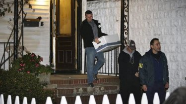 FBI agents remove evidence from the Brooklyn, New York residence of Rabbi Mendel Epstein, who was among four Orthodox Jewish rabbis and one of their sons who were indicted.