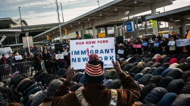 A group of Muslim men pray while supporters hold up signs during an interfaith prayer and rally against the ban at John F. Kennedy Airport.