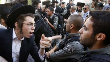 Protest ... police struggle face ultra-orthodox Jews at a rally in Jerusalem.