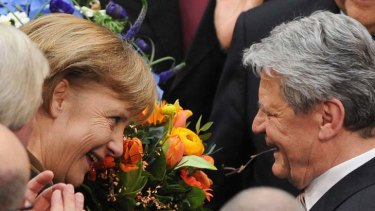 Blooming freedom … the German Chancellor, Angela Merkel, hands a bouquet to the new President, Joachim Gauck, on Sunday.