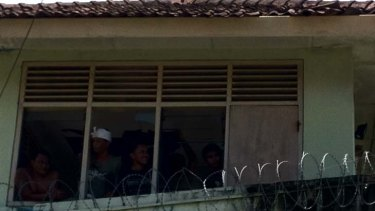 Prisoners are still in control of Kerobokan prison with some pictured here in a guard tower.