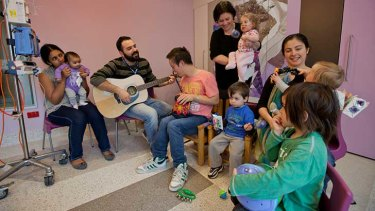 Rodrigo Quiroga playing guitar with patients at a children's hospital