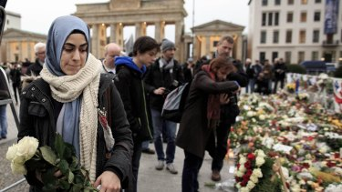 A young Muslim woman holds white roses outside the French Embassy among candles, messages and flowers left by mourners commemorating the victims of the terrorist attacks in Paris.