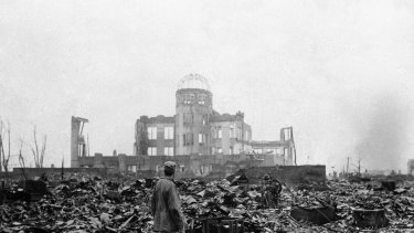 An Allied correspondent stands in the rubble of a building that once was a movie theatre in Hiroshima, on Sepember 8, 1945, after the first nuclear weapon ever used in warfare was dropped by the US on August 6, 1945.