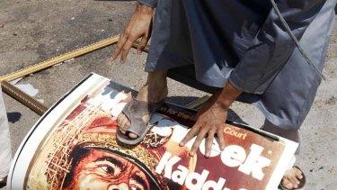 A man steps on a poster of Libya's leader Muammar Gaddafi.