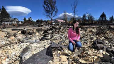 Taylor Yoakum, 19, looks for family heirlooms in her destroyed home in Weed, California.
