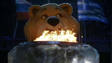 A robotic bear pauses before extinguishing the Olympic flame.