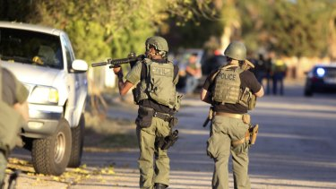 Police at the scene of a shootout about a mile from the site in San Bernardino where gunmen left at least 14 dead.