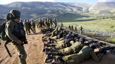 On guard ... Israeli troops take positions along the damaged border fence after Palestinian demonstrators trampled it.