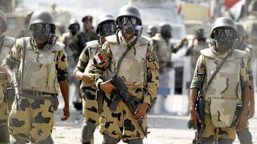Army soldiers wear gas masks before clashes with members of the Muslim Brotherhood and supporters of deposed Egyptian President Mohamed Mursi at Republican Guard headquarters in Nasr City, a suburb of Cairo.