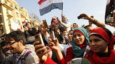Young Egyptian men and women use their mobile phones to record the celebrations in Egypt's Tahrir Square at the overthrow of President Hosni Mubarak.