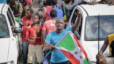 A demonstrator holds the Burundi national flag and makes the victory sign as he and others celebrate the military coup d'etat, in the capital Bujumbura, Burundi.