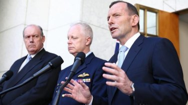 Prime Minister Tony Abbott, with Defence Minister David Johnston and chief of the Defence Force Air Chief Marshal Mark Binskin, announces the security committee's decision.