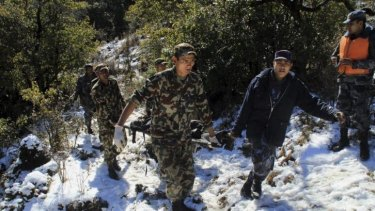 Recovery effort ... Nepalese policemen, in blue uniform, and army men carry the body of one of those killed in a plane crash at Khachikot in Argakhanchi district, in western Nepal.