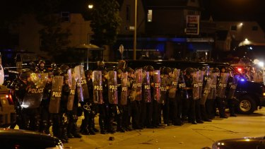 Police are pelted with rocks and shots rang out in Milwaukee, Sunday, Aug. 14, 2016. Police said one person was shot at a Milwaukee protest on Sunday and officers used an armored vehicle to retrieve the injured victim and take the person to a hospital, as tense skirmishes erupted for a second night following the police shooting of a black man. (AP Photo/Jeffrey Phelps)