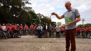Andrew Zoerner, the father of Nicholas Ruygrok's fiancee, drops rose petals at the site of the fatal crash as members of the Dulwich Hill Bicycle Club look on.