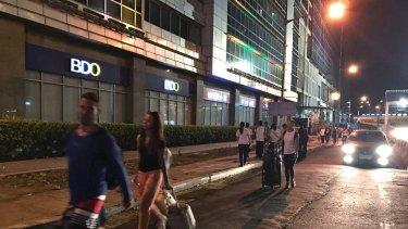 People walk with their luggage outside the Resorts World Manila complex.