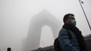 A pedestrian wearing a face mask walks past China Central Television headquarters building, which is shrouded in haze.