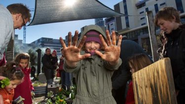 A young resident gets her hands dirty at the new community garden in Docklands.