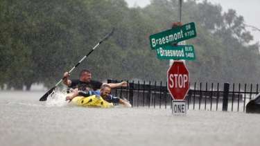 Two men try to beat the current pushing them down a road in Houston during Hurricane Harvey's deluge in August.