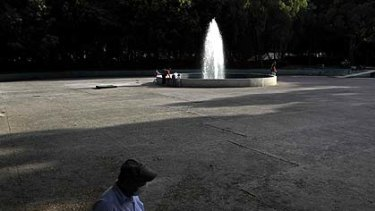 A man with a protective face mask passes a nearly empty park as a few children play in the fountain in Mexico City.