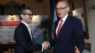 Australian Foreign Minister Bob Carr (right) is greeted by his Indonesian counterpart Marty Natalegawa.