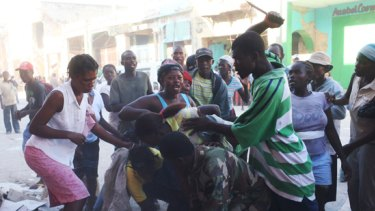 Haitians fight for goods from a damaged business.