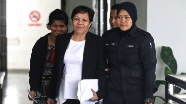 Australian Maria Elvira Pinto Exposto, centre, is escorted by a police officer during a court hearing in Malaysia earlier this month.