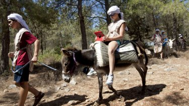 American tourist Ella uses an iPad while riding a wi-fi-outfitted donkey lead by her brother Aaron, in Kfar Kedem, a biblical reenactment park in the village of Hoshaya in the Galilee, northern Israel.