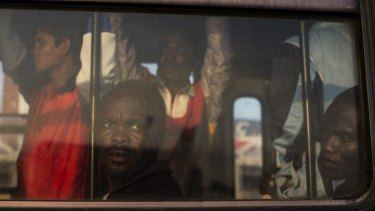 Perilous voyage: Refugees from Nigeria and Ghana wait on a bus to be taken to temporary accommodation after arriving to Sicily.