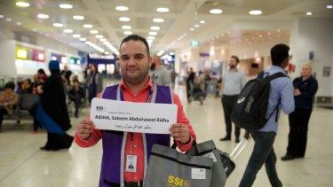 """Adam Bujairami, a """"welcome-to-Australia"""" official, awaits the Ridha family, from Iraq, at Sydney International Airport."""