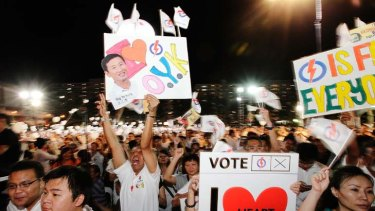 People's Action Party supporters carry signs in support of the Aljunied GRC team, led by the Foreign Minister, George Yeo.