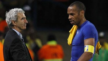 Thierry Henry, right, shakes hands with coach Raymond Domenech as he leaves the pitch after France's loss to South Africa.