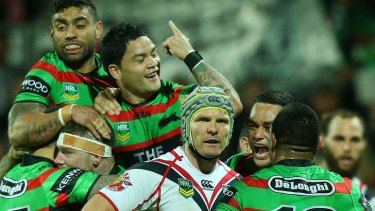 Odd man out: Warrior Todd Lowrie can't look as Souths celebrate another try.