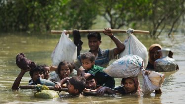 A Rohingya family fleeing Myanmar reaches the Bangladesh border after crossing a creek.