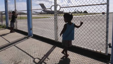Nauruans watch a Royal Australian Air Force C-17 Globemaster III. The plane's arrival this week was a first step in creating a new immigration detention centre there.     20120824 airport7.jpg