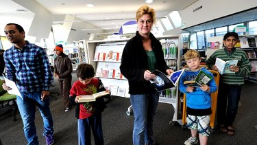 Jack Attard, Sally Attard and Josh Maiden enjoy books at the Altona North Library. Councils say the cuts could affect staffing and opening hours.