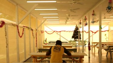 A man sits inside the Nauru off shore processing centre in 2007 ... The opposition immigration spokesman, Scott Morrison, has claimed Nauru can be reopened and run for a third of  the Immigration Department's $2 billion estimate.