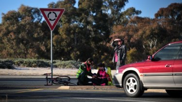A cyclist is attended to by an ambulance officer after being hit by a vehicle at a roundabout in Kambah (file photo).