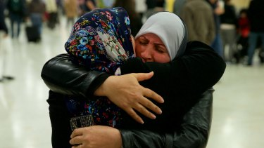 For the first time in nearly a decade, Dhekra Mohsin, at right, hugs her daughter Zahra Aobadah, who has been in a Turkish refugee camp with her husband and four daughters.