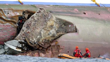 A rock emerges from the side of the luxury cruise ship.