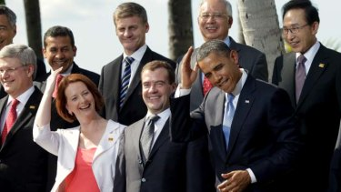 Camera ready ... Barack Obama jokingly mimics Julia Gillard's hair-grooming gesture at the APEC leaders meeting photo call on Sunday.
