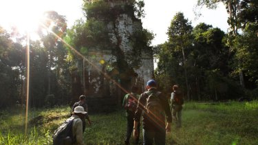 Archaeologists approach the Thom Dab temple in the Siem Reap region.