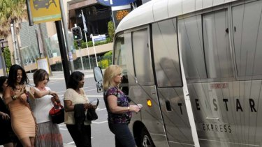 People queue to catch the free shuttle bus from in front of Bankstown Sports Club to The Star yesterday.